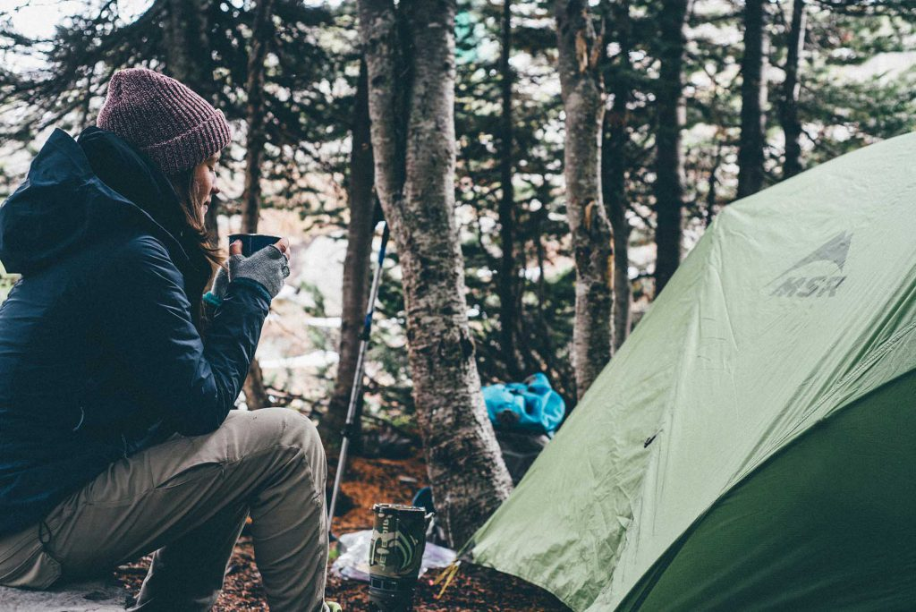 Woman drinking hot beverage in campsite, trekking tips for beginners