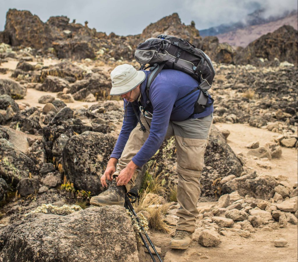 Tying trekking boots on Kilimanjaro hike