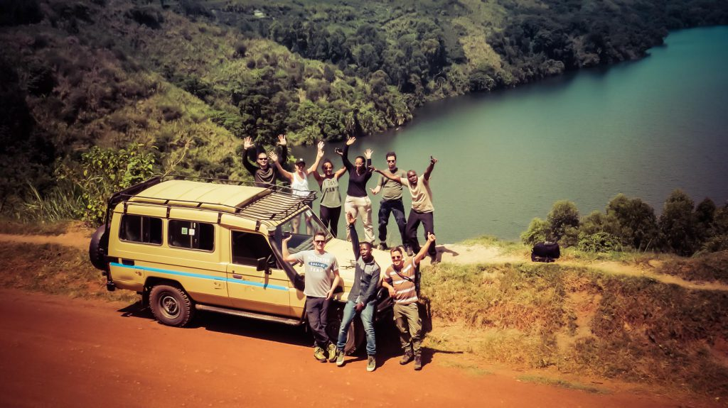 Friends on safari by vehicle and lake