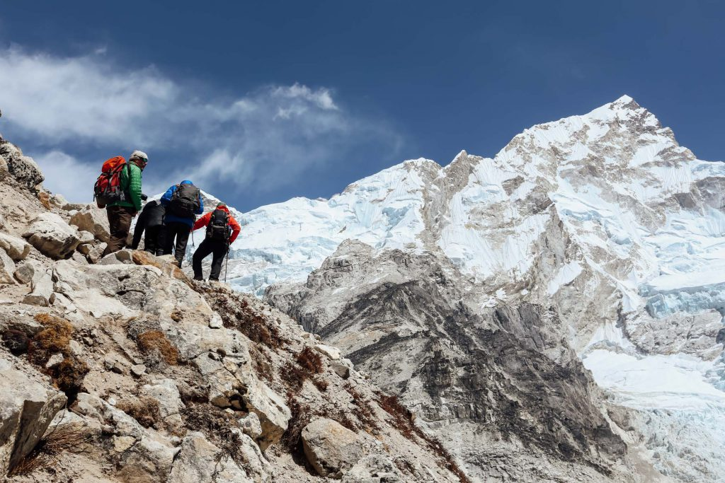 Trekkers climbing a mountain using trekking poles