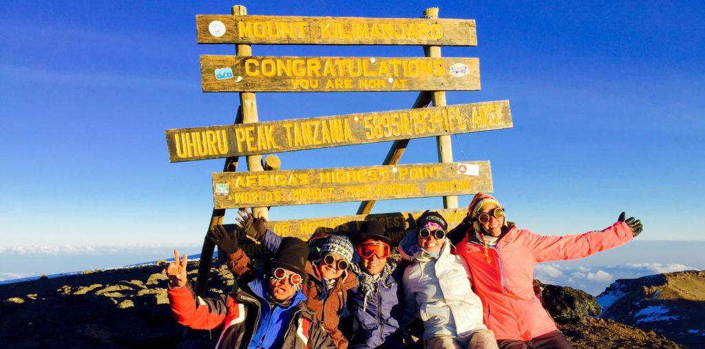 Five friends standing in front of a sign on Mount Kilimanjaro