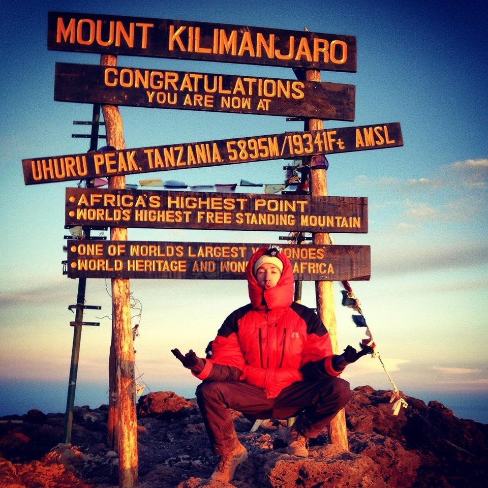 Man sitting by sign for Uhuru Peak on Kilimanjaro