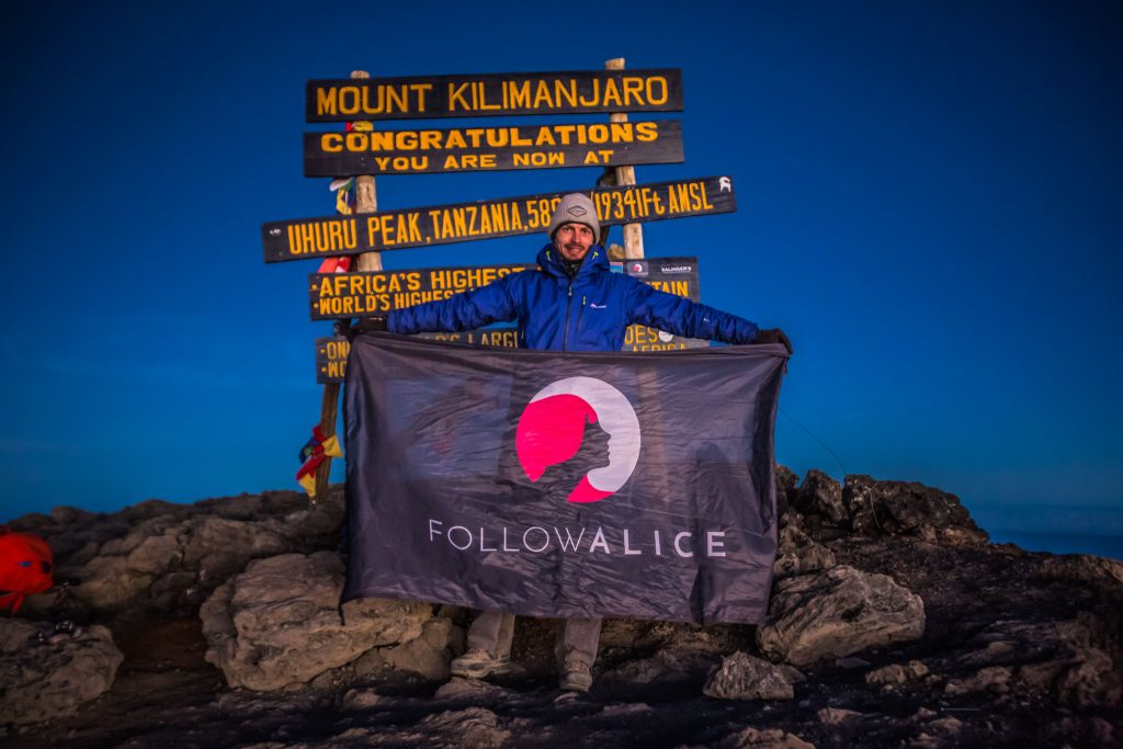 Man holds a flag on Kilimanjaro