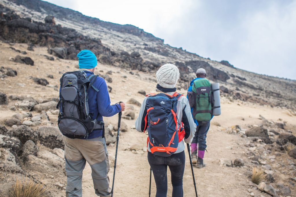 3 people with backpacks climbing Kilimanjaro