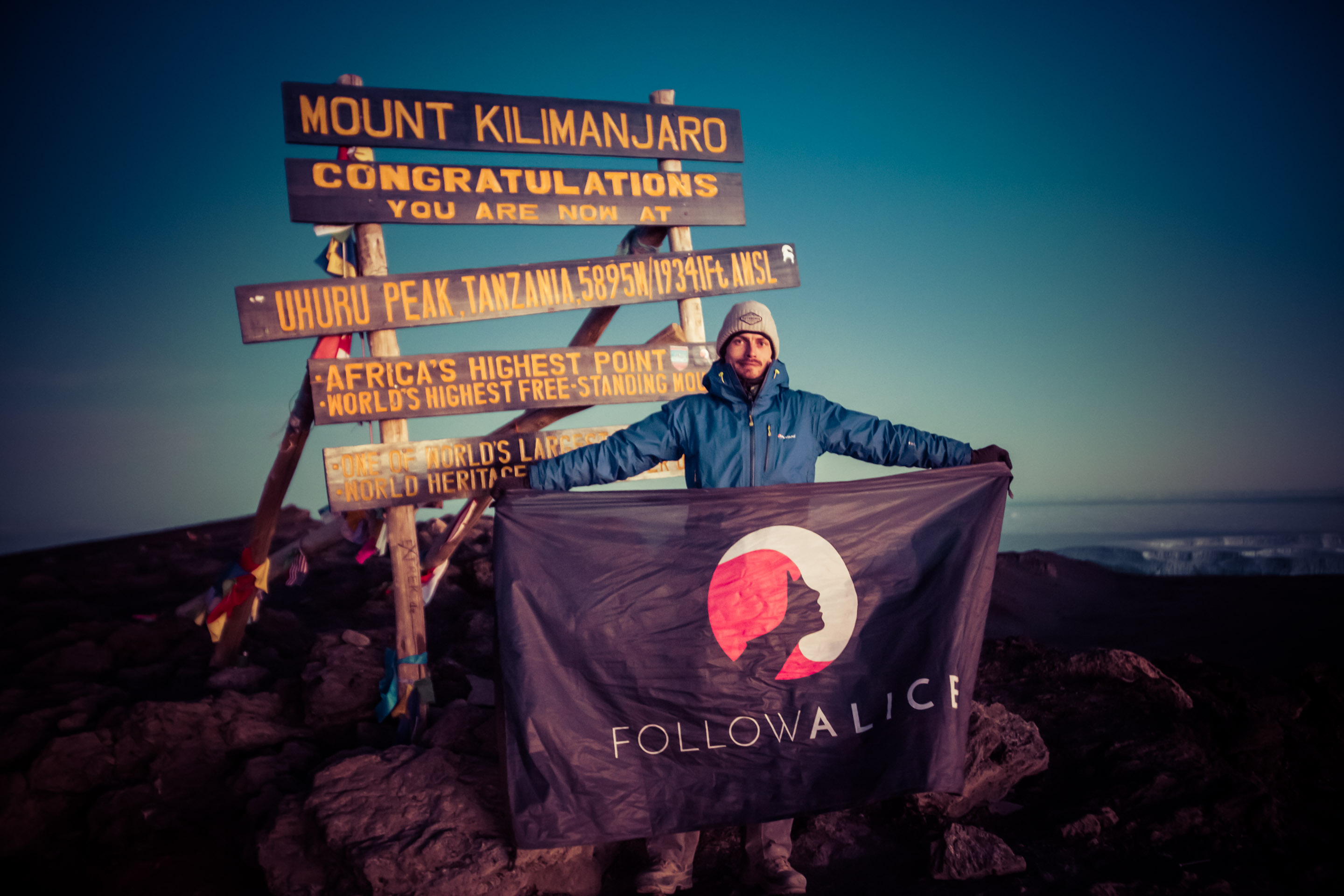 Ambassador Dan flying the Follow Alice flag at the summit of Mount Kilimanjaro