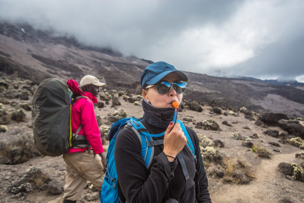 Lady drinking water and man with backpack on mount Kilimanjaro
