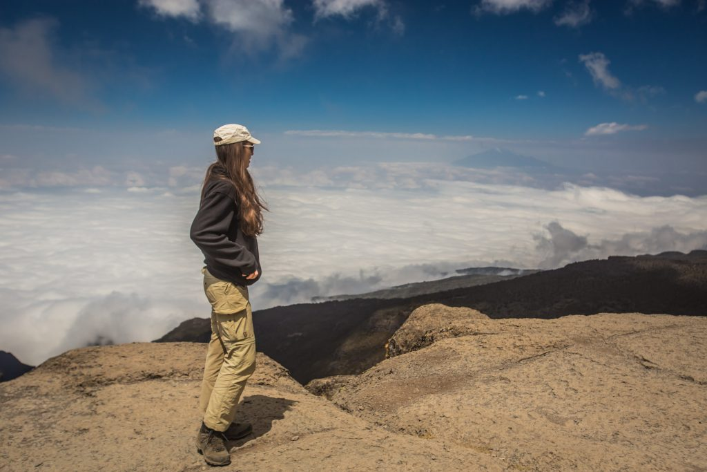 Lady overlooking the clouds on Mount Kilimanjaro