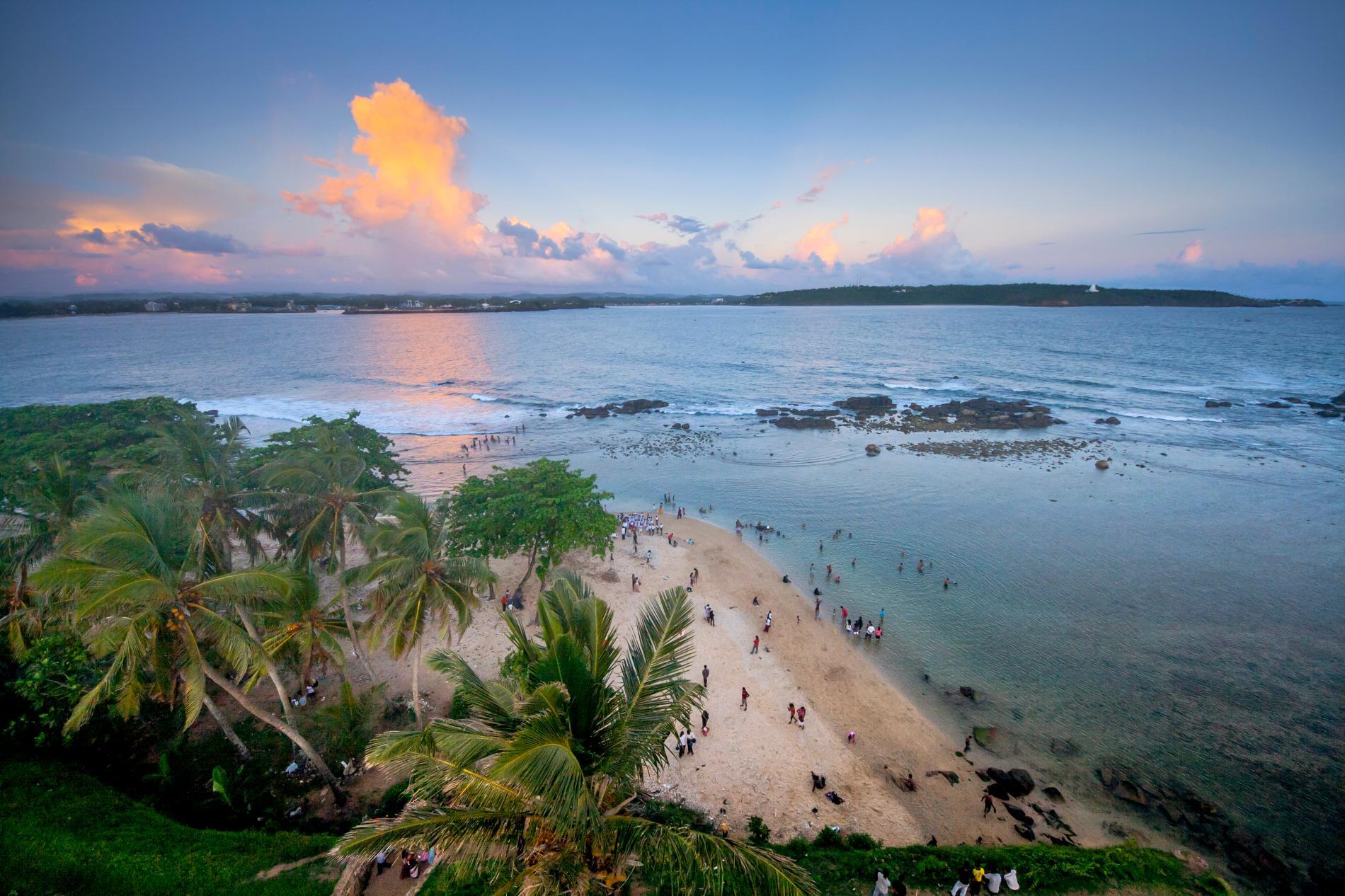 Beachgoers enjoy the coast beneath the Galle Fort on the southwestern coast of Sri Lanka.