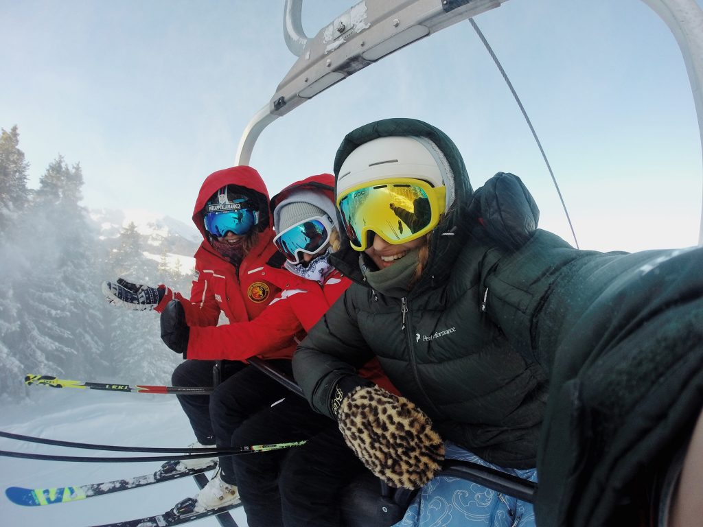 Skiers in chairlift in the Alps