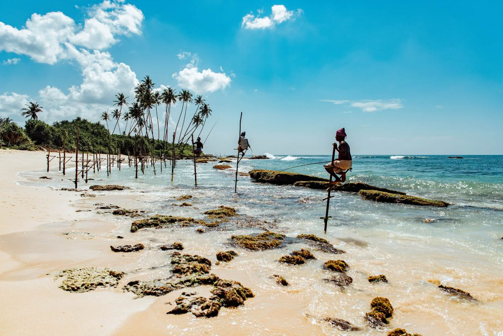 Stilt fisherman on beach in Sri Lanka