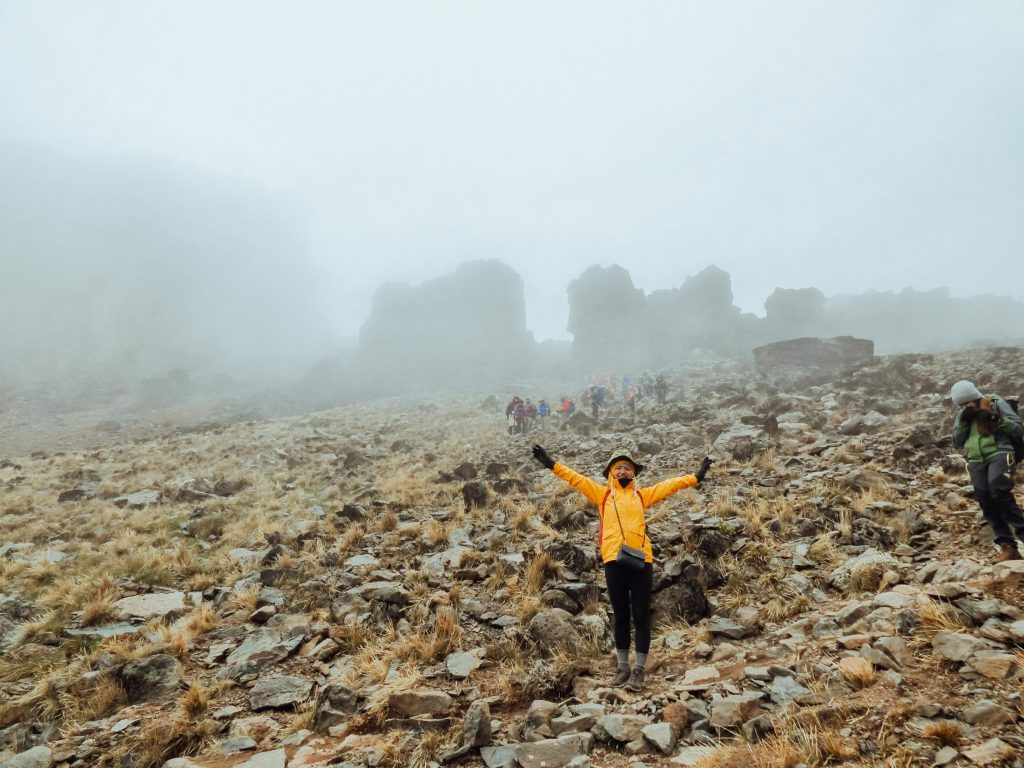 Happy climber in yellow jacket on Kilimanjaro in the mist