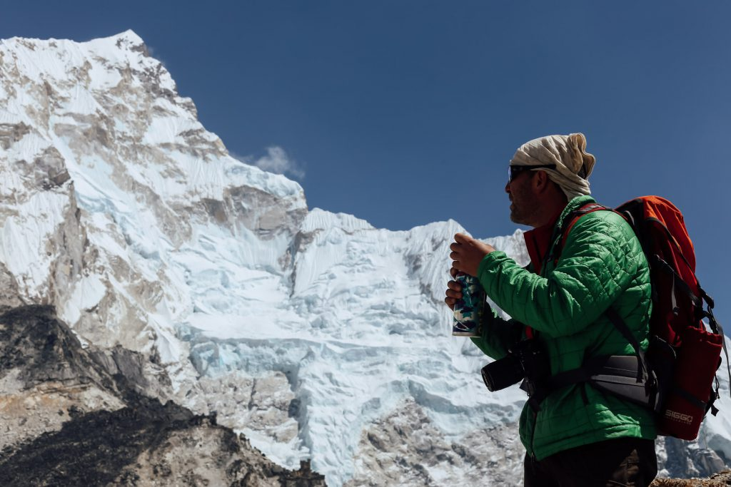 Man with backpack drinking out of water bottle with mountains behind him