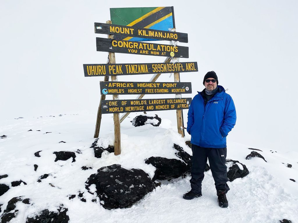 Man Standing Kilimanjaro Summit Sign
